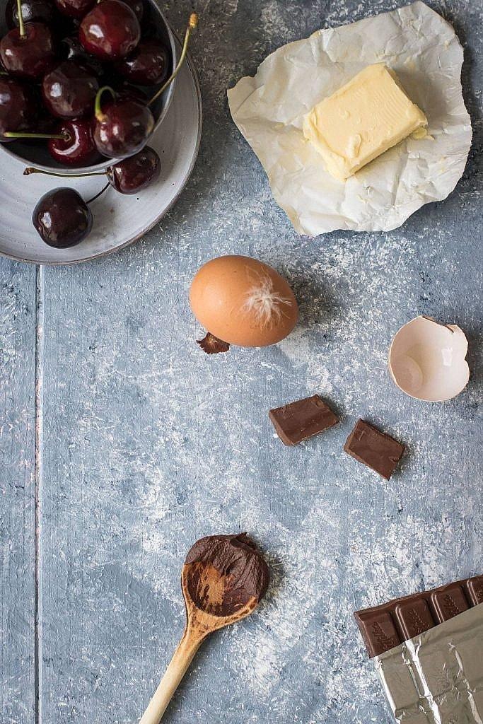 Kirschen, Eier, Butter und Schokolade für saftigen Schokokuchen auf Tisch