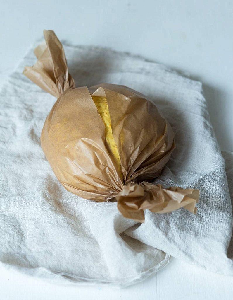 Kürbisbrot in Backpapier eingewickelt auf Küchentuch