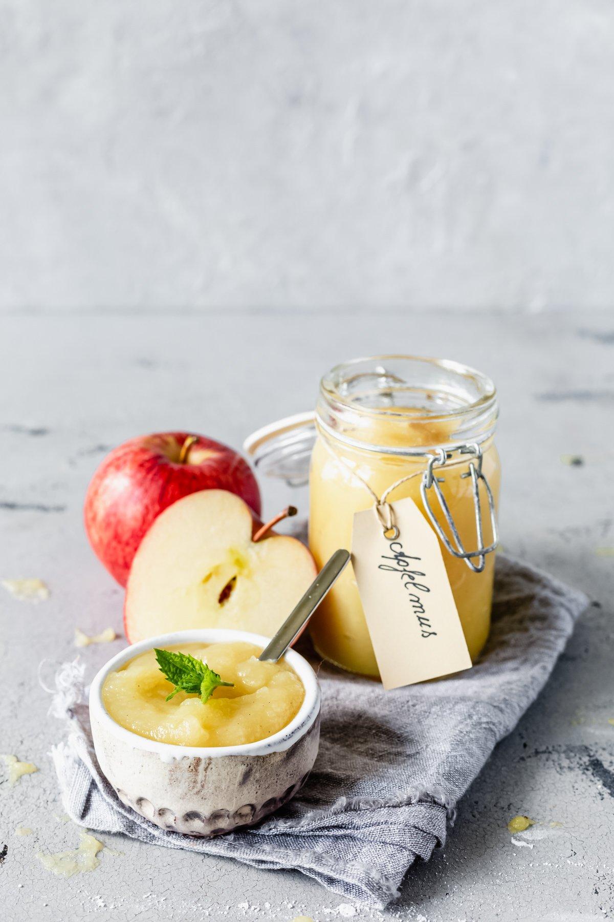 Selbstgemachtes Apfelmus im Glas mit Äpfeln und kleinem Schälchen