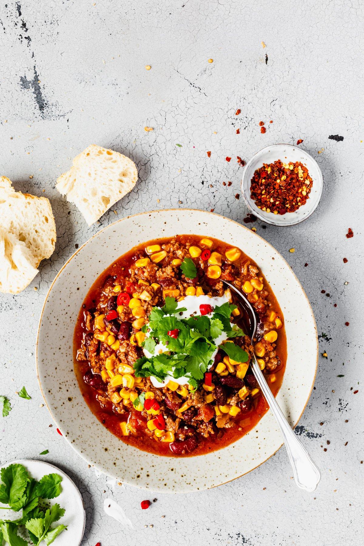 Chili con Carne mit Löffel und Zutaten auf Tisch